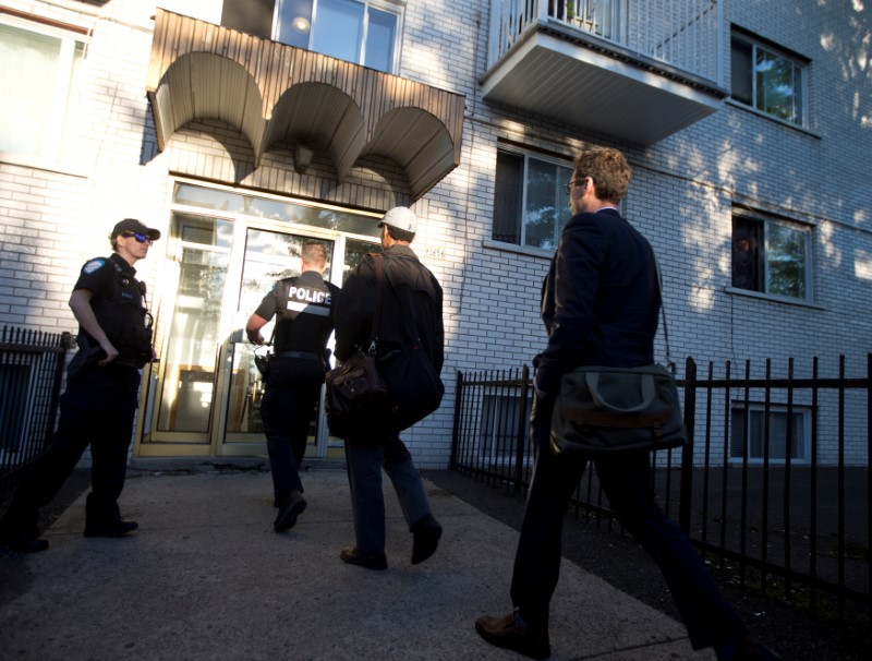 Police investigators walk into the residence of Amor Ftouhi, in Montreal, Quebec, Canada on June 21, 2017. (REUTERS/Christinne Muschi)