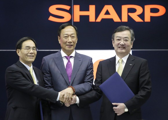 Chairman of Taiwan's Hon Hai Precision, also known as Foxconn, Terry Guo (C) and Vice Chairman Tai Jeng-wu (L) pose with President of Japan's Sharp Kozo Takahashi (R) during a press conference in Osaka, western Japan, on April 2, 2016.     Sharp agreed to be bought by Taiwanese multinational Hon Hai Precision, the world's biggest electronics supplier. (STR/AFP/Getty Images)