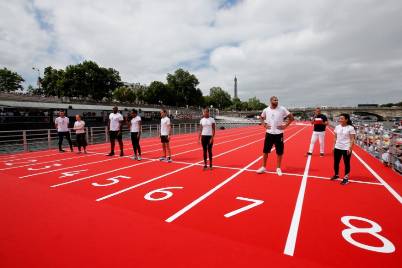 French athletes (L-R) G. Gilles, Nantenin Keita, Teddy Rinner, Marie-Jose Perec, Renaud Lavillenie, Heather Arneton, Nicolas Batum, Sarah Ourahmoune pose before the start for a 100m race on an athletics track installed on the River Seine in Paris, France, June 23, 2017 as Paris transforms into a giant Olympic park to celebrate International Olympic Days with a variety of sporting events for the public across the city during two days as the city bids to host the 2024 Olympic and Paralympic Games.  REUTERS/Jean-Paul Pelissier