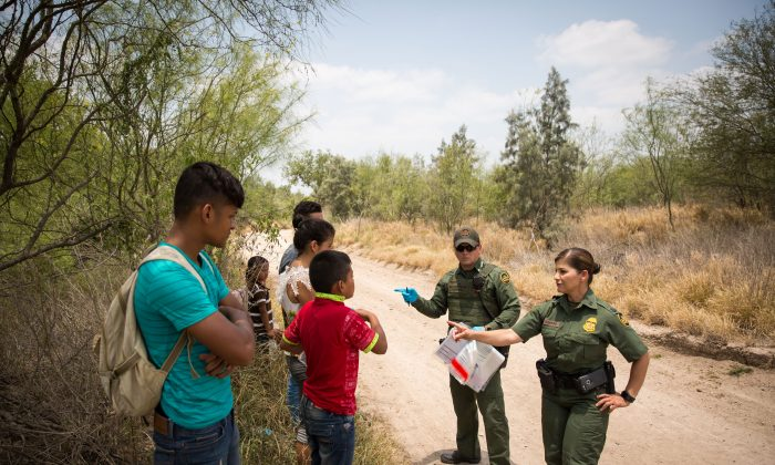 Border Patrol Agents talk to unaccompanied minors who just crossed over the US–Mexico border, before loading them in a van for transport to an Office of Refugee and Resettlement facility, in Hidalgo County, Texas, on May 26, 2017. (Benjamin Chasteen/The Epoch Times)
