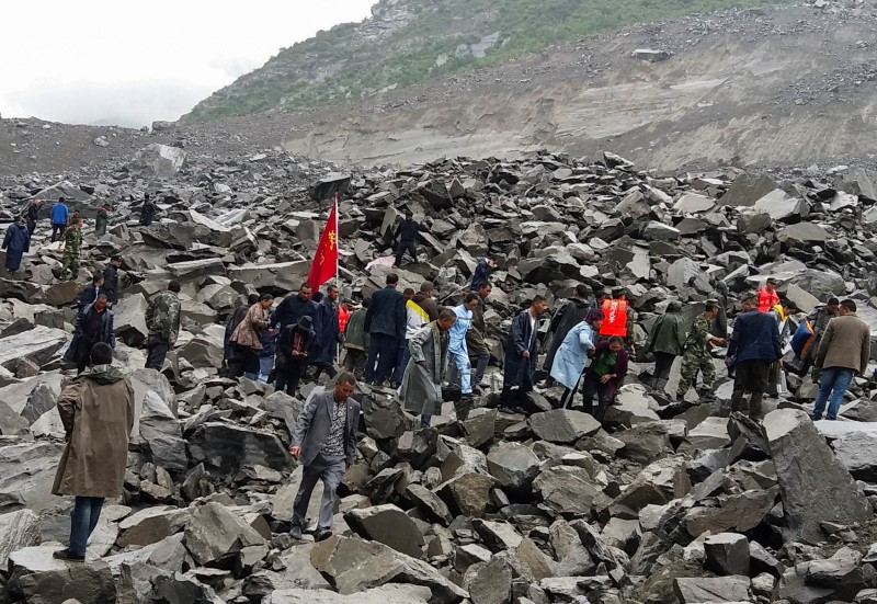 People search for survivors at the site of a landslide that destroyed some 40 households, where more than 100 people are feared to be buried, according to local media reports, in Xinmo Village, China on June 24, 2017. (REUTERS/Stringer)