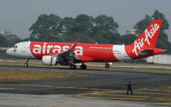 In this file photo, an Indian airport staff member walks next to an AirAsia airplane after it landed on its inaugural flight from New Delhi to Bagdogra Airport on February 19, 2017. (Diptendu Dutta/AFP/Getty Images)