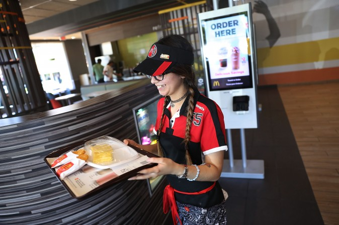 McDonald's crew member Crystalle Martin carries an order to a customers table as the McDonald's restaurant on April 25, 2017 in Miami, Florida. (Joe Raedle/Getty Images)