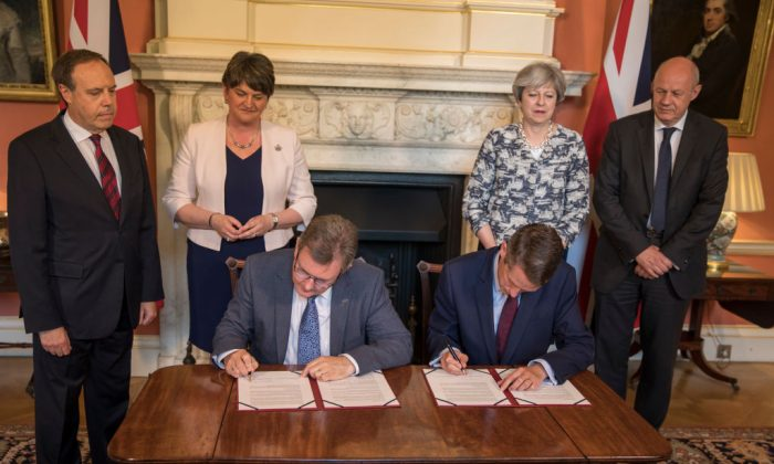 Prime Minister Theresa May (2R) stands with First Secretary of State Damian Green (R), Democratic Unionist Party (DUP) leader Arlene Foster (2L), DUP Deputy Leader Nigel Dodds (L) while DUP MP Jeffrey Donaldson (3L) and Parliamentary Secretary to the Treasury, and Chief Whip, Gavin Williamson sit and sign paperwork inside 10 Downing Street in London, England on June 26, 2017. (Jack Hill - WPA Pool /Getty Images)