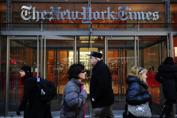 People walk by the entrance to US newspaper 'The New York Times' in New York, March 8, 2011. (EMMANUEL DUNAND/AFP/Getty Images)