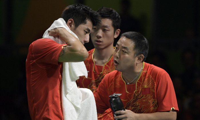 China's Zhang Jike (L) is counseled by his coach Liu Guoliang (R) after losing a game in the men's team semi-final table tennis match against South Korea at the Riocentro venue during the Rio 2016 Olympic Games in Rio de Janeiro on August 15, 2016. (JUAN MABROMATA/AFP/Getty Images)