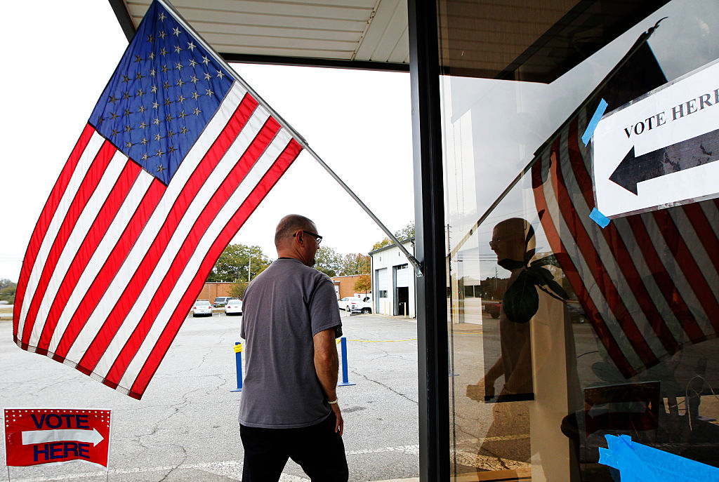 A voter walks past a US flag as he heads in to vote in the US presidential election at the Athens-Clarke County Fleet building in Athens, Georgia on Nov. 8, 2016. (TAMI CHAPPELL/AFP/Getty Images)