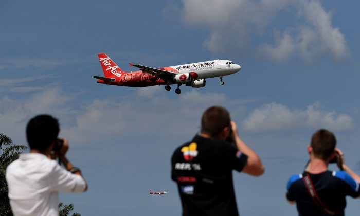 Plane spotters take photographs of an AirAsia A320 airbus as it prepares to land at the Kuala Lumpur International Airport 2 (KLIA 2) in Sepang on May 5, 2017. (MANAN VATSYAYANA/AFP/Getty Images)