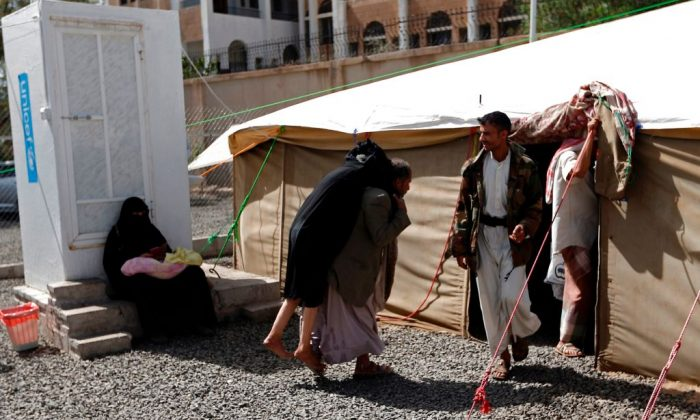 A Yemeni man carries a woman suspected of being infected with cholera as they arrive for treatment at Sabaeen Hospital in Sanaa, on June 13, 2017. (MOHAMMED HUWAIS/AFP/Getty Images)