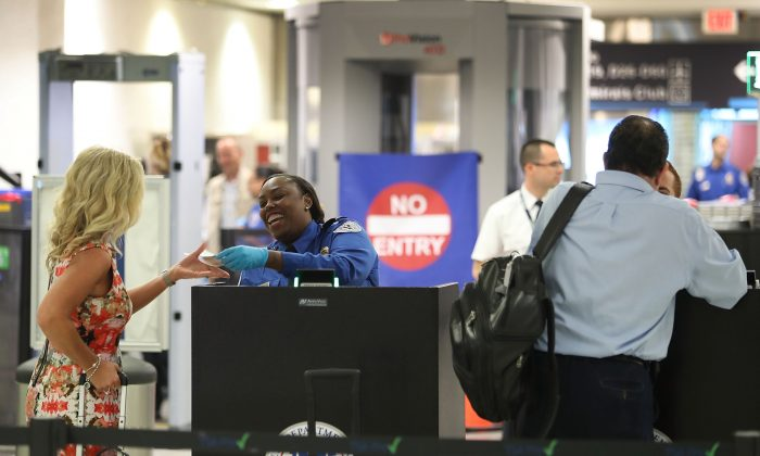 TSA agents check the documents of travelers as they go through the TSA PreCheck security point at Miami International Airport on June 2, 2016 in Miami, Florida. (Joe Raedle/Getty Images)