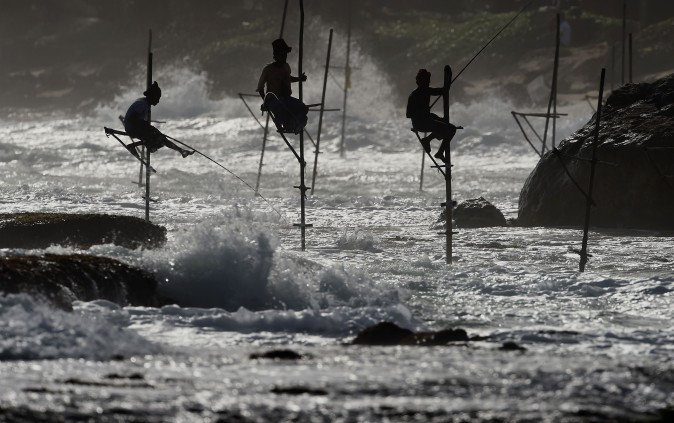 Sri Lankan stilt fishermen on their poles as they fish in the southern town of Galle on July 1. (ISHARA S. KODIKARA/AFP/Getty Images)