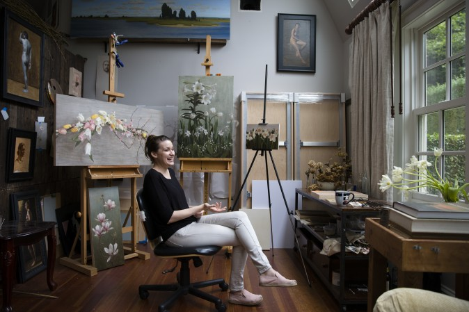 Karie G. Whipple signs her painting in her studio in Southampton on June 23, 2017. (Samira Bouaou/The Epoch Times)