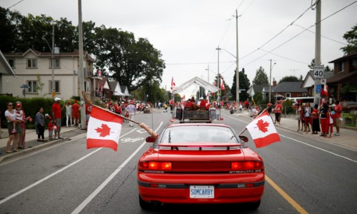 "People hold Canadian flags with hockey sticks from inside a car during the East York Toronto Canada Day parade, as the country marks its 150th anniversary with ""Canada 150"" celebrations, in Toronto, Ontario, Canada on July 1, 2017. (REUTERS/Mark Blinch)"