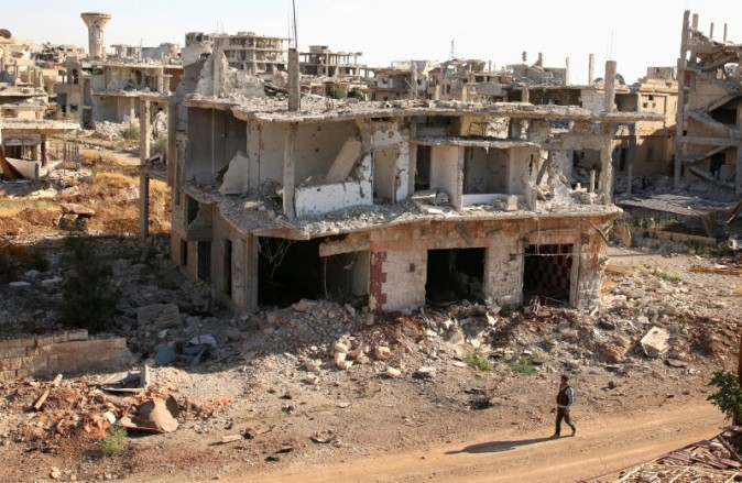A rebel fighter walks past damaged buildings in a rebel-held part of the southern city of Deraa Syria
