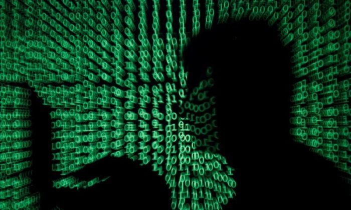 A man holds a laptop computer as cyber code is projected on him in this illustration picture taken on May 13, 2017. (Reuters/Kacper Pempel/Illustration/File Photo)
