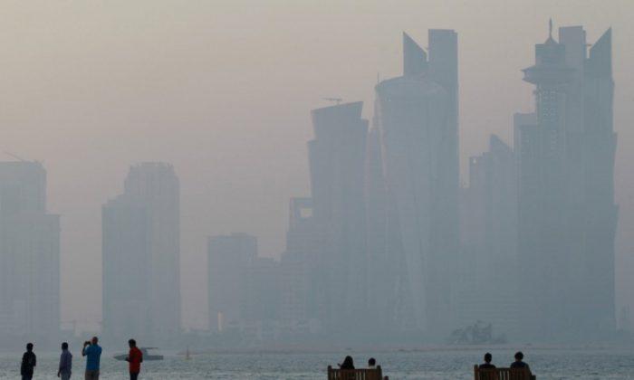 People sit on the corniche in Doha, Qatar on June 15, 2017. (REUTERS/Naseem Zeitoon)