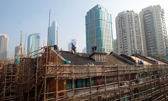 Laborers renovate a roof of a residential lane house in Shanghai on Aug. 21, 2014. (JOHANNES EISELE/AFP/Getty Images)
