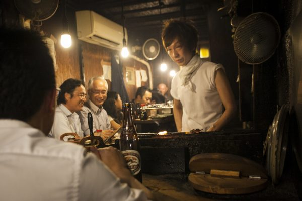 A vendor inside the Omoide Yokocho tends to grilled chicken skewers, or yakitori. (Annie Wu/The Epoch Times)