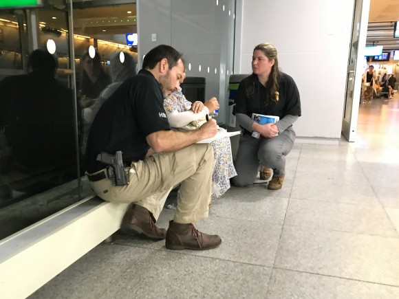 Agents from Homeland Security Investigations speak to the mother of a 14-year-old girl who is about to fly alone to Egypt, at JFK International Airport on June 26, 2017. The agents are concerned the young girl may be subject to female genital mutilation once in Egypt. (Benjamin Chasteen/The Epoch Times)