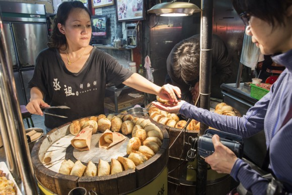 A vendor sells a popular pastry cake at Shilin Night Market. (Rayman Cheuk Wai-man/Shutterstock)