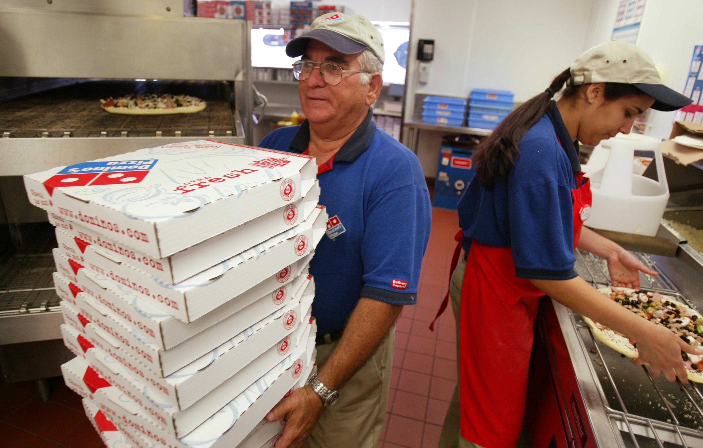 Elio Blanco (L) and Yenelis Garcia prepare pizzas at Domino's Pizza in Miami, Fla., on April 14, 2004. (Joe Raedle/Getty Images)