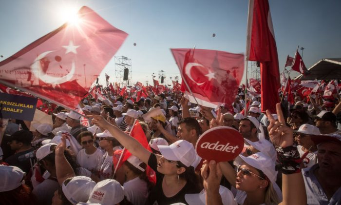 """Thousands of supporters cheer and wave flags while listening to Turkey's main opposition Republican People's Party (CHP) leader Kemal Kilicdaroglu speak on stage during the """"Justice Rally"""" in Istanbul, Turkey on July 9, 2017. (Chris McGrath/Getty Images)"""