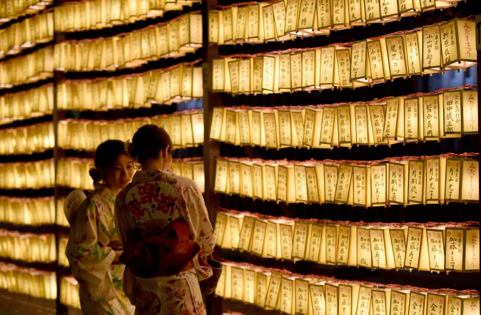 Women walk among rows of lit lanterns during the Mitama Matsuri festival at the Yasukuni Shrine in Tokyo on July 13, 2017. Some 30,000 lanterns were illuminated in the precinct in memory of the war victims. (TORU YAMANAKA/AFP/Getty Images)