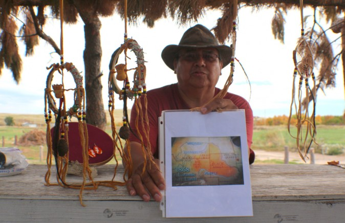 Emerson Elk following his mission of teaching visitors from a map highlighted in orange The Big Horn Mountains, Greasy Grass and Black Hills Territory ceded to the Oglala Sioux Tribe under the Treaty of 1886 and the Ft. Laramie Treaty. (Myriam Moran copyright 2014)
