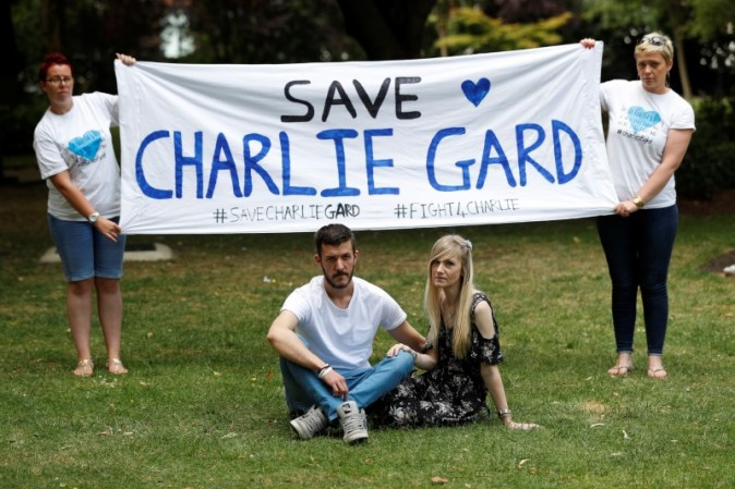 Connie Yates and Chris Gard, pose for photographers as supporters hold a banner before delivering a petition to Great Ormond Street Hospital in central London on July 9, 2017. (REUTERS/Peter Nicholls)