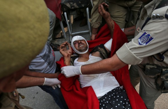 A man who was injured after a bus he was travelling in skidded off a mountain road and fell into a gorge in Jammu and Kashmir's Ramban district, is rushed to a hospital for treatment in Jammu July 16, 2017. (Reuters/Mukesh Gupta)