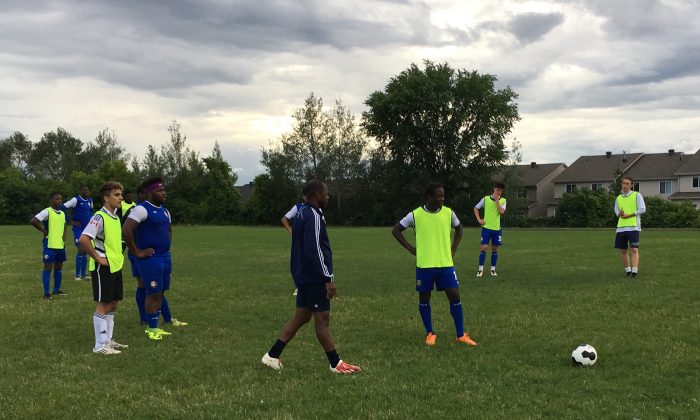 X-Uvia coach Richard Morris (dark top) stops play and explains what a striker should be looking to do during a practice game at Samuel Genest High School in Ottawa on June 27, 2017. (Rahul Vaidyanath/The Epoch Times)