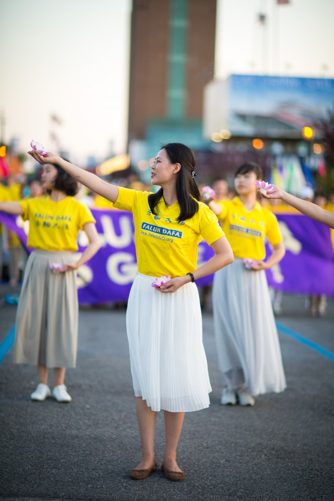 Woman perform a song and dance at a rally in front of Chinese Consulate in New York calling for an end to the Falun Gong persecution inside China in New York on July 16, 2017. (Benjamin Chasteen/The Epoch Times)