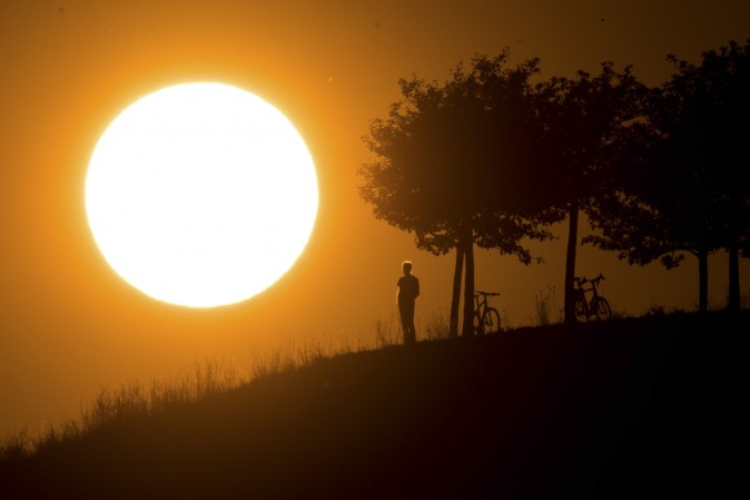 A man looks at the setting sun near Hanover, northern Germany, on July 17, 2017. (JULIAN STRATENSCHULTE/AFP/Getty Images)