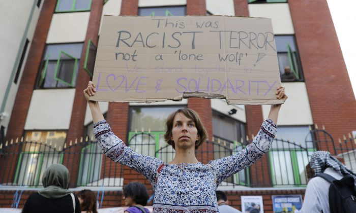A woman's sign at a vigil outside Finsbury Park Mosque illustrates how the attack there brought up the issue of how terrorism is defined. (TOLGA AKMEN/AFP/Getty Images)