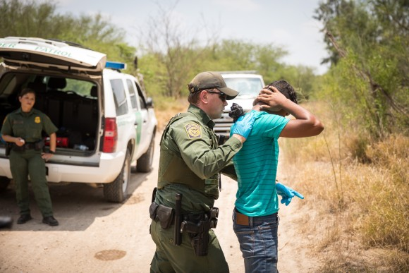 A Border Patrol agent pats down a Honduran man who has just crossed the Rio Grande from Mexico in Hidalgo County, Texas, on May 26. (Benjamin Chasteen/The Epoch Times)