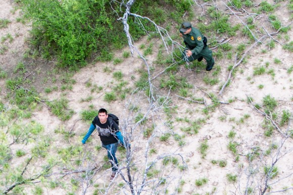 An illegal alien (L) looks up at a Customs and Border Protection helicopter while being pursued by a Border Patrol agent after trying to evade capture, near Salineno, Texas, on May 30. (Benjamin Chasteen/The Epoch Times)
