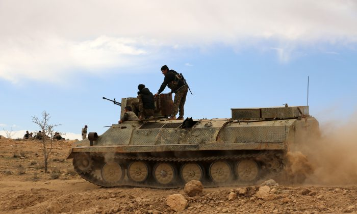 Fighters from the Syrian Democratic Forces (SDF) sit atop an armoured personnel carrier on the outskirts of the town of al-Shadadi in the northeastern Syrian province of Hasakeh, on Feb. 19, 2016. (DELIL SOULEIMAN/AFP/Getty Images)