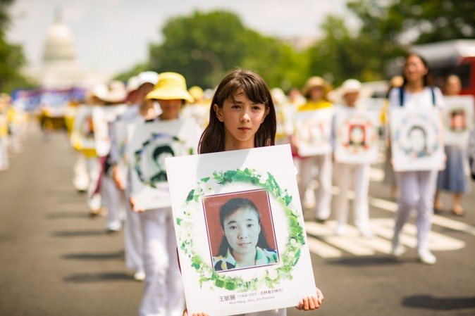 Falun Gong practitioners hold wreaths with photos of people who were killed in China for their beliefs. Hundreds of practitioners of the spiritual discipline marched in a parade in Washington on July 20, 2017, calling for an end to the persecution that started in China on July 20, 1999. (Benjamin Chasteen/The Epoch Times)
