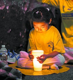 A girl attends a candlelight vigil in front of the Chinese Consulate in New York on July 16. (BENJAMIN CHASTEEN/THE EPOCH TIMES)