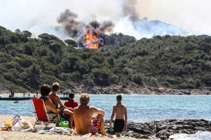 People on the beach look at a forest fire in La Croix-Valmer, France, on July 25, 2017. Firefighters battled blazes that have consumed swathes of land in southeastern France for a second day, with one inferno out of control near the chic resort of Saint-Tropez. (VALERY HACHE/AFP/Getty Images)