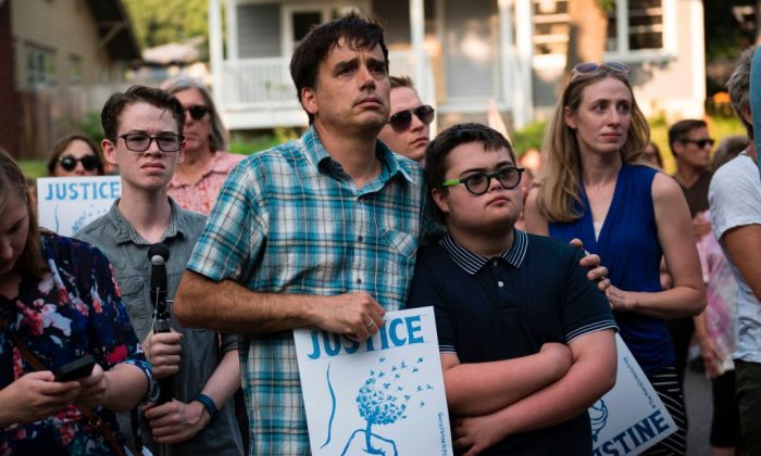 Marchers look on as Don Damond, fiance of Justine Damond, greets demonstrators outside his home on July 20, 2017 in Minneapolis, Minnesota. (STEPHEN MATUREN/AFP/Getty Images)
