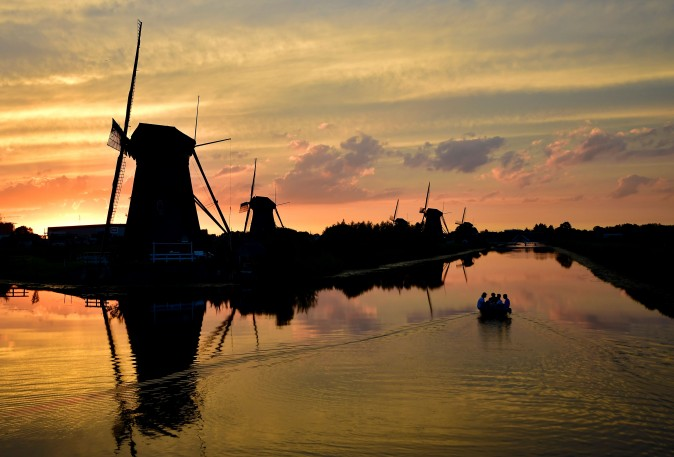 People sail on a small boat at sunset in the village of Kinderdijk in the Netherlands on July 31, 2017. (TOBIAS SCHWARZ/AFP/Getty Images)