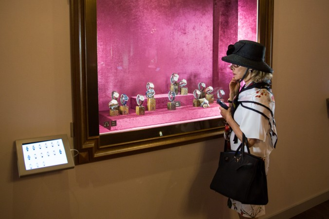 """A woman looks at the current collection of Patel Philippe at """"The Art of Watches Grand Exhibition"""" in New York on July 19, 2017. (Benjamin Chasteen/The Epoch Times)"""