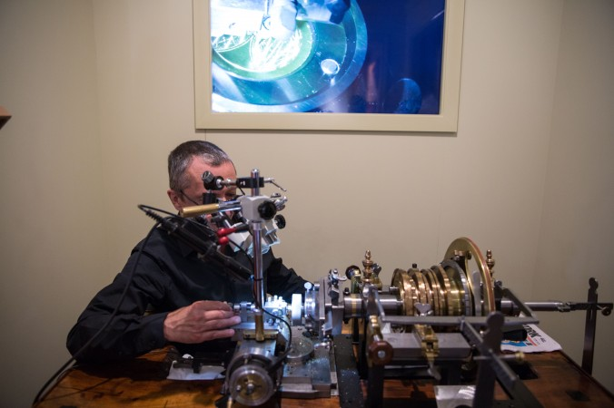 """An artisan uses a guilloché machine to engrave the dial of a watch at Patek Philippe's """"The Art of Watches Grand Exhibition"""" in New York on July 19, 2017. (Benjamin Chasteen/The Epoch Times)"""