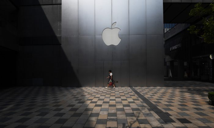 """A woman walks past an Apple store in Beijing on August 3, 2017.  Apple has removed software allowing internet users to skirt China's """"Great Firewall"""" from its app store in the country, the company confirmed, sparking criticism that it was bowing to Beijing's web censorship. (Greg Baker/AFP/Getty Images)"""