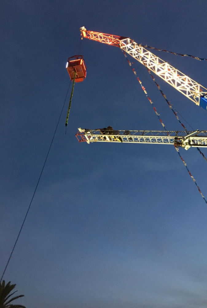 Fire fighters use ropes to rappel down a ride operator and customer from a cage suspended by a crane at the Ventura City County Fair on Aug 2. (Ventura City Fire Dept.)