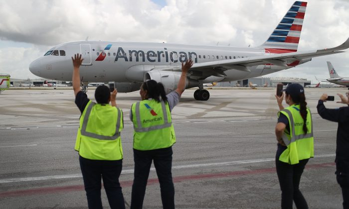 Employees wave to an American Airlines flight on the tarmac in a file photo. (Joe Raedle/Getty Images)