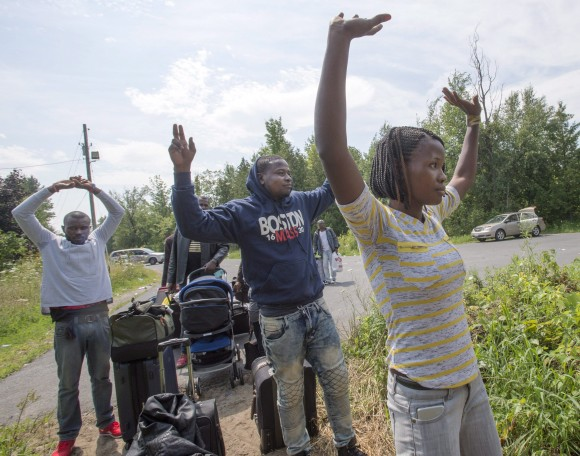 A group of asylum seekers raise their arms as they approach RCMP officers while crossing the Canadian border at Champlain, N.Y., on Aug. 4, 2017. (The Canadian Press/Ryan Remiorz)