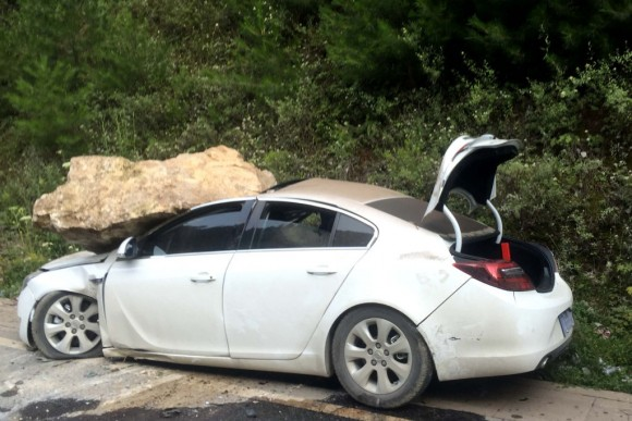 A car, damaged by a rock during an earthquake, is seen in Jiuzhaigou in China's southwestern Sichuan province on August 9, 2017.  At least 12 people were killed when a 6.5-magnitude earthquake struck southwestern China, government sources said on August 9, but the toll was expected to climb as news trickles out of the remote mountainous region. / AFP PHOTO / STR / China OUT        (Photo credit should read STR/AFP/Getty Images)