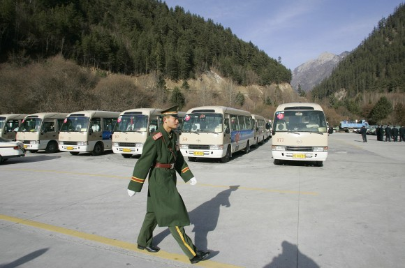 """JIUZHAIGOU, CHINA:  A Chinese paramilitary soldier inspects parking area at Jiuzhaigou Nine-village valley) in the Aba Tibetan and Qiang Autonomous Prefecture in China's southwestern province of Sichuan, 09 January 2006. The famous attraction tourism Jiuzhaigou Valley is known as the """"fairyland on the Earth"""", was listed by the World Heritage Council of UNESCO into the Catalogue of World Natural Heritage in 1992.  AFP PHOTO/ LIU Jin  (Photo credit should read LIU JIN/AFP/Getty Images)"""